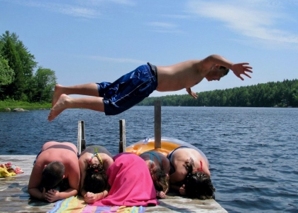 Boy diving over his friends